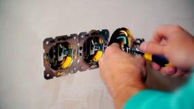 As mãos do eletricista instalam os soquetes de parede bondes video estoque
