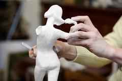 As mãos do escultor funcionam com statuette. fotografia de stock royalty free