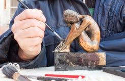 As mãos do escultor guardam a escultura de cobre e limpam-na com a escova Fotografia de Stock Royalty Free