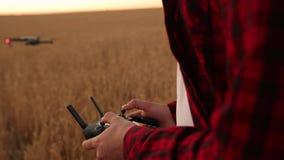 As mãos do fazendeiro guardam o controlador remoto com suas mãos quando o quadcopter voar no fundo O zangão paira atrás do filme