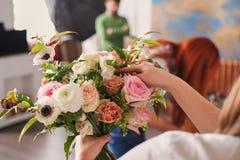 as mãos do florista recolhem o ramalhete do casamento no trabalho imagens de stock