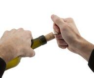 As mãos do homem abrem a garrafa do vinho Imagens de Stock Royalty Free