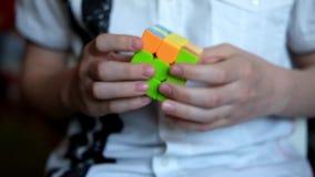 As mãos do homem aceleraram a tentativa resolver o cubo de Rubik com caras redondas filme