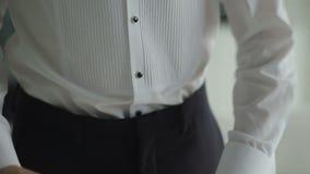 As mãos do homem apertam na moda sua calças preta filme