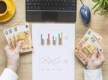 As mãos do homem com dinheiro no desktop Desktop do escritório no fundo de madeira Vista superior Euro- Equilíbrio de contas imagens de stock