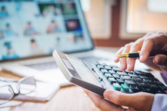 As mãos do homem de negócios com calculadora e o custo no escritório e no F foto de stock
