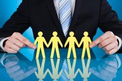 As mãos do homem de negócios que guardam a corrente de papel dos povos na mesa Imagens de Stock