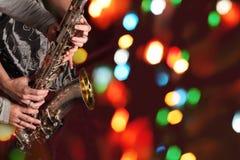 As mãos do homem e da mulher com o saxofone em luzes do bokeh fotografia de stock royalty free