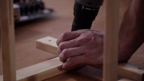 As mãos do homem estão funcionando com a chave de fenda eletrônica moderna para conectar pranchas vídeos de arquivo