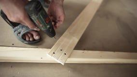 As mãos do homem estão usando a chave de fenda mecânica verde para parafusar a prancha de madeira amarela vídeos de arquivo
