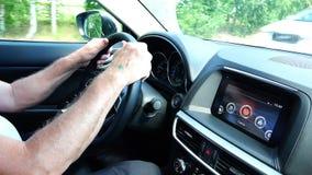 As mãos do homem idoso guardam o volante do carro e conduzem o veículo vídeos de arquivo