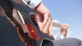 As mãos do homem jogam a guitarra Cordas tocantes da guitarra do guitarrista Feche acima do tiro vídeos de arquivo