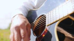 As mãos do homem jogam a guitarra Cordas tocantes da guitarra do guitarrista Feche acima do tiro video estoque