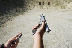 As mãos do homem que carregam a arma na escala de acendimento Imagens de Stock Royalty Free