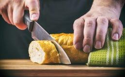 As mãos do homem que cortam o pão na prancha de madeira Imagens de Stock