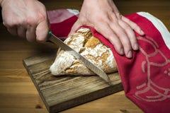 As mãos do homem que cortam o pão na prancha de madeira Fotografia de Stock Royalty Free