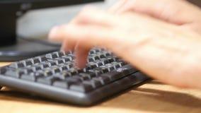 As mãos do homem que datilografam no teclado do portátil, trabalhando no projeto no computador em linha filme
