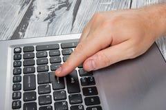 As mãos do homem que datilografam o teclado do portátil que faz o pagamento em linha em casa contra a tabela de madeira Conceito  Fotografia de Stock