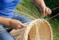 As mãos do homem que fazem uma cesta de vime imagem de stock royalty free