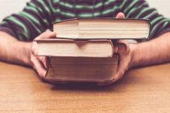 As mãos do homem que guardam alguns livros velhos Fotografia de Stock
