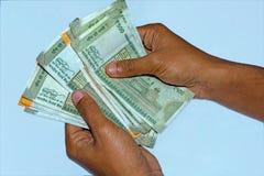 As mãos do homem que guardam e que contam 500 e 200 rupias novas da moeda indiana imagens de stock