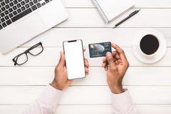 As mãos do homem que guardam o cartão vazio do smartphone e de crédito fotografia de stock royalty free
