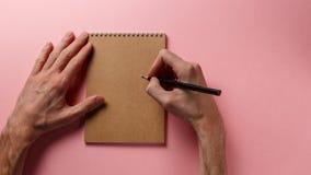 As mãos do homem que guardam o lápis e o bloco de notas espiral fotografia de stock