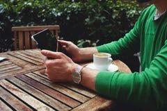 As mãos do homem que guardam a tabuleta digital que senta-se na tabela de madeira no terraço da cafetaria imagens de stock royalty free