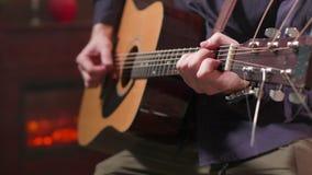 As mãos do homem que guardam uma guitarra acústica e que executam uma composição video estoque