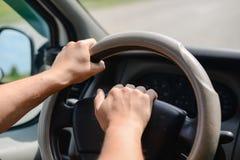 As mãos do homem que guardam uma roda de um carro e que soam a Foto de Stock Royalty Free
