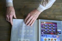 As mãos do homem superior guardam o álbum de selo com coleção de selos postais, tema do espaço, fundo de madeira imagem de stock