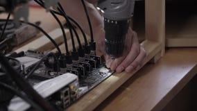 As mãos do homem usam a chave de fenda eletrônica para conectar o cartão-matriz à prancha de madeira filme
