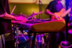 As mãos do músico que jogam o teclado em um espetáculo ao vivo na fase com outros homens que jogam guitarra foto de stock