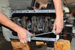 As mãos do mecânico esticam o tampão de rolamento do eixo de manivela motor a combustão interna com uma chave de torque Fotografia de Stock