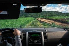 As mãos do motorista da mulher no volante para dentro de um carro, estrada de terra do campo, offroad, fora da estrada, volta do  fotos de stock