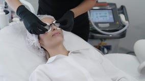 As mãos do movimento lento do esteticista nas luvas põem sobre vidros protetores especiais nos olhos pacientes vídeos de arquivo