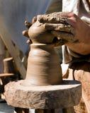 As mãos do oleiro funcionam uma roda de oleiro Imagens de Stock