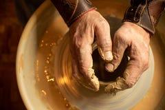 As m?os do oleiro mestre est?o em um produto pequeno da argila que seja ficado situado em uma m?quina especial imagens de stock royalty free