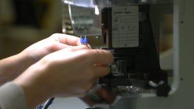 As mãos do operário estão funcionando na máquina e em fios bondes de conexão vídeos de arquivo