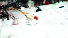 As mãos do operário estão funcionando na máquina e em fios bondes de conexão filme