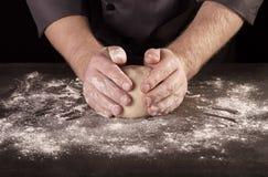 As mãos do padeiro amassaram a protuberância da massa na tabela com farinha, no preto imagem de stock