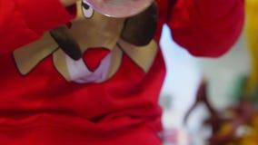 As mãos do rapaz pequeno estão agitando a bola da neve sob a forma do carro Tempo do Natal vídeos de arquivo