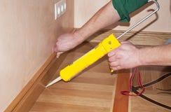 As mãos do reparador que instalam o assoalho de madeira do carvalho da placa de contorno com calafetação de Gu foto de stock
