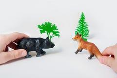 As mãos do ` s da criança estão jogando com figuras animais da floresta em um fundo branco foto de stock royalty free