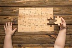 As mãos do ` s da criança recolhem um enigma no fundo de uma tabela de madeira imagens de stock