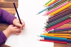 As mãos do ` s da criança são pintadas com lápis coloridos em uma folha de papel branca em uma tabela de madeira fotos de stock royalty free