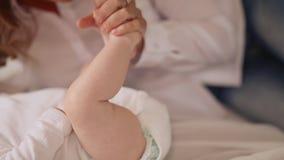 As mãos do ` s da mãe tocam delicadamente nos pés pequenos de seu bebê filme