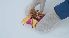 As mãos do ` s da menina nos mitenes aumentam um presente que se encontre na neve filme