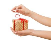 As mãos do ` s da mulher abrem a caixa atual, colhem, cortam Fotos de Stock Royalty Free