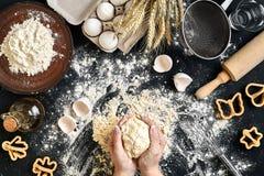 As mãos do ` s da mulher amassam a massa na tabela com farinha, ovos e ingredientes Vista superior Fotografia de Stock